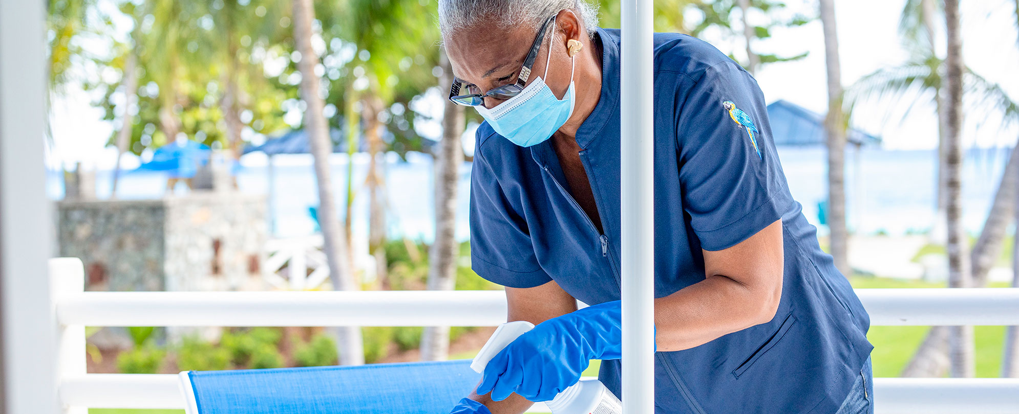 A Margaritaville Vacation Club housekeeper sanitizing outdoor seating.