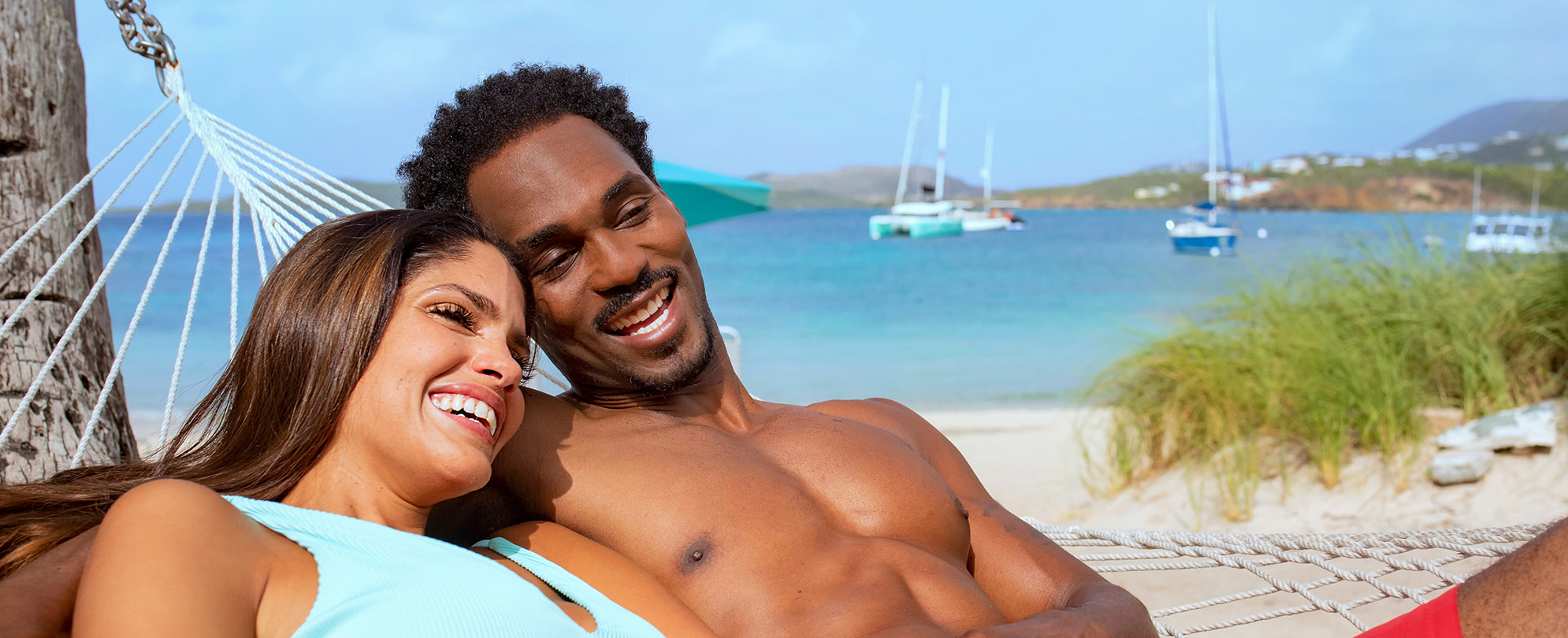Man and woman smiling, laying in a hammock by the ocean at a Margaritaville Vacation Club timeshare resort.