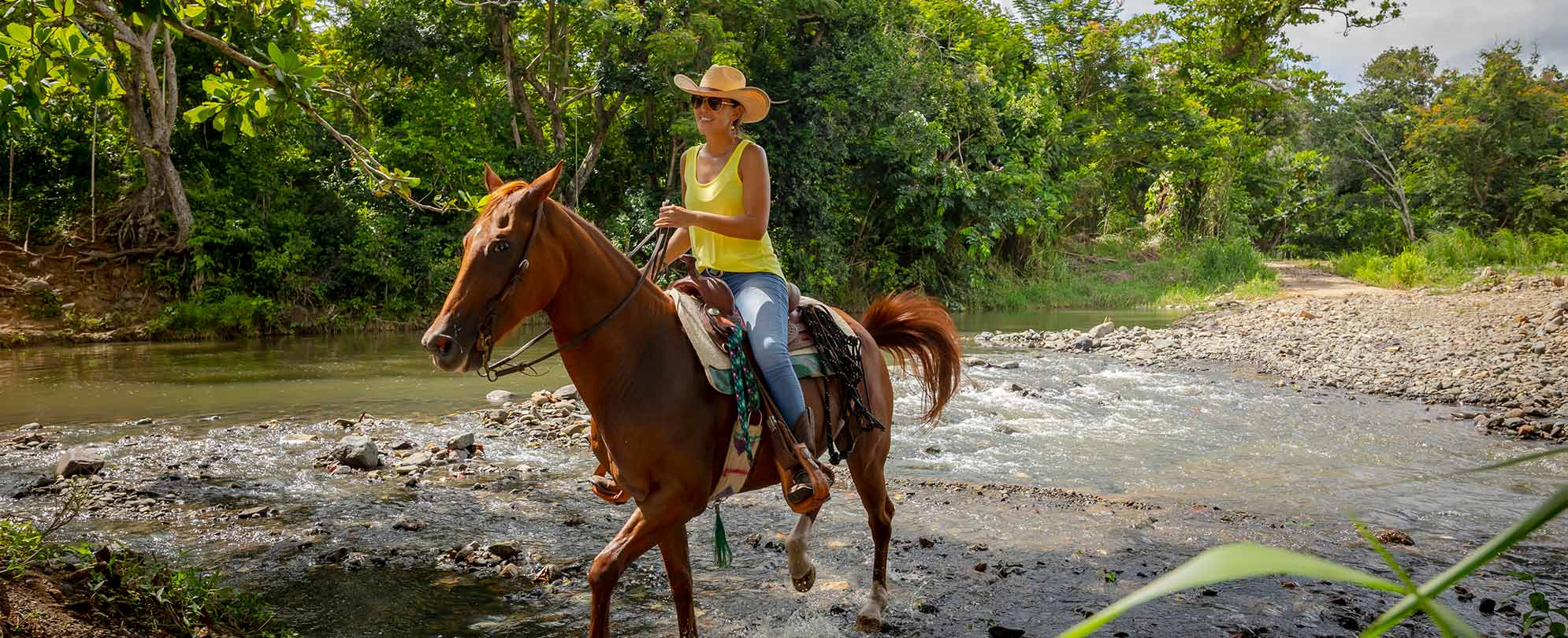 A woman wearing a yellow tank top and a wide-brimmed hat riding a horse through a rocky river.
