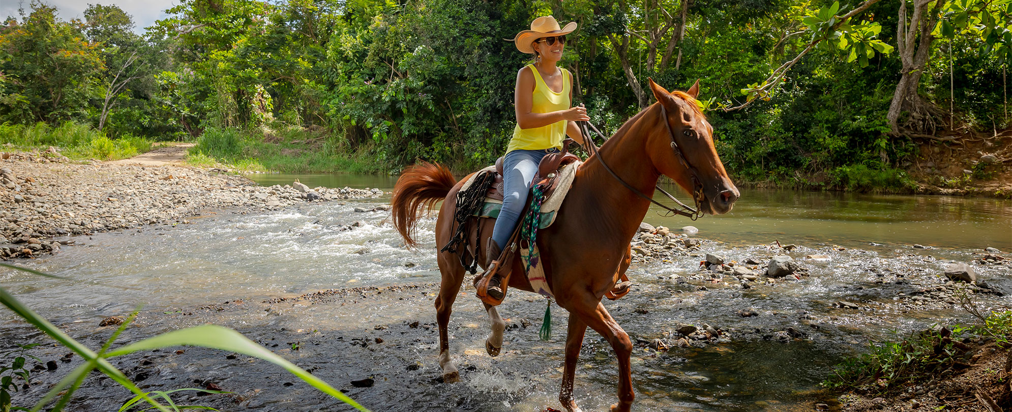 Woman wearing a yellow tank top and a wide-brimmed hat riding a horse through a rocky river.