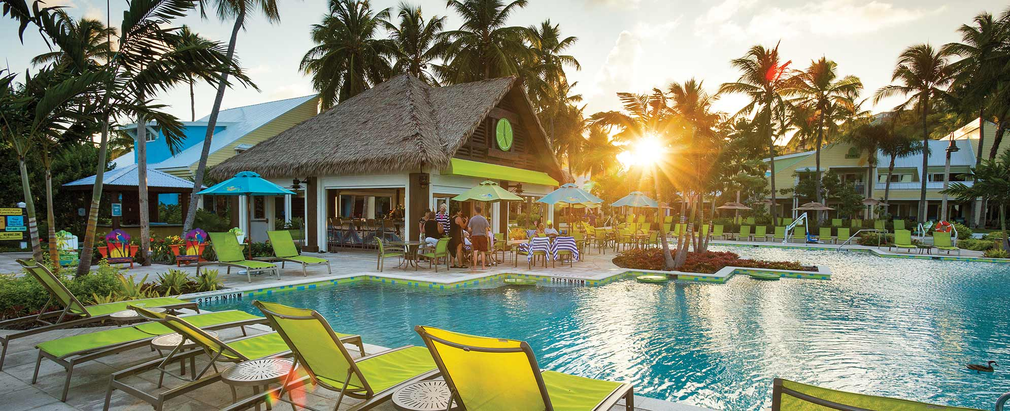 The sun sets on the pool, tiki bar, and bright green pool chairs at Margaritaville Vacation Club by Wyndham - St. Thomas.
