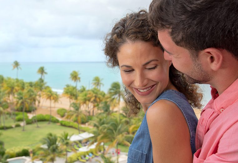 Man and woman smile on the balcony of their Margaritaville Vacation Club suite, with palm trees and ocean in the background.