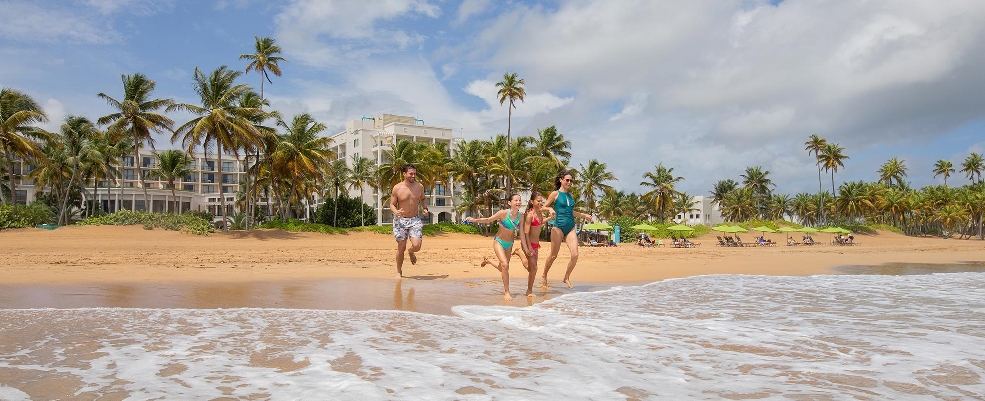 Mom, dad, and two young daughters running into the ocean on vacation at Margaritaville Vacation Club by Wyndham - Rio Mar.