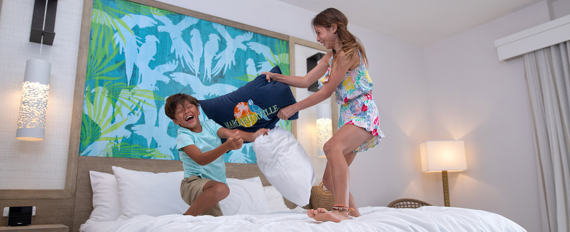 Young girl and boy laughing while having a pillow fight on a bed in a Margaritaville Vacation Club resort suite.