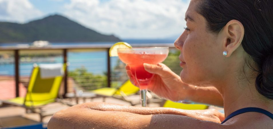 Dark-haired woman looks out over the ocean with a pink margarita in hand, relaxing at a Margaritaville Vacation Club resort.