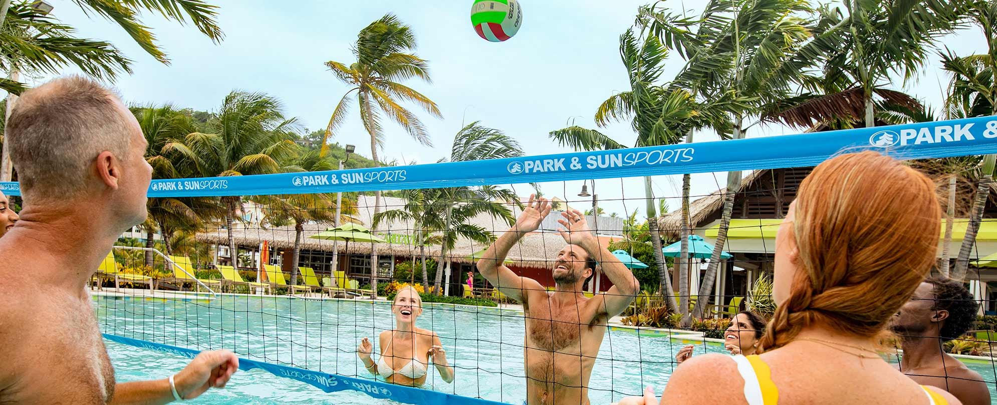 A family playing volleyball in a Margaritaville Vacation Club resort pool.