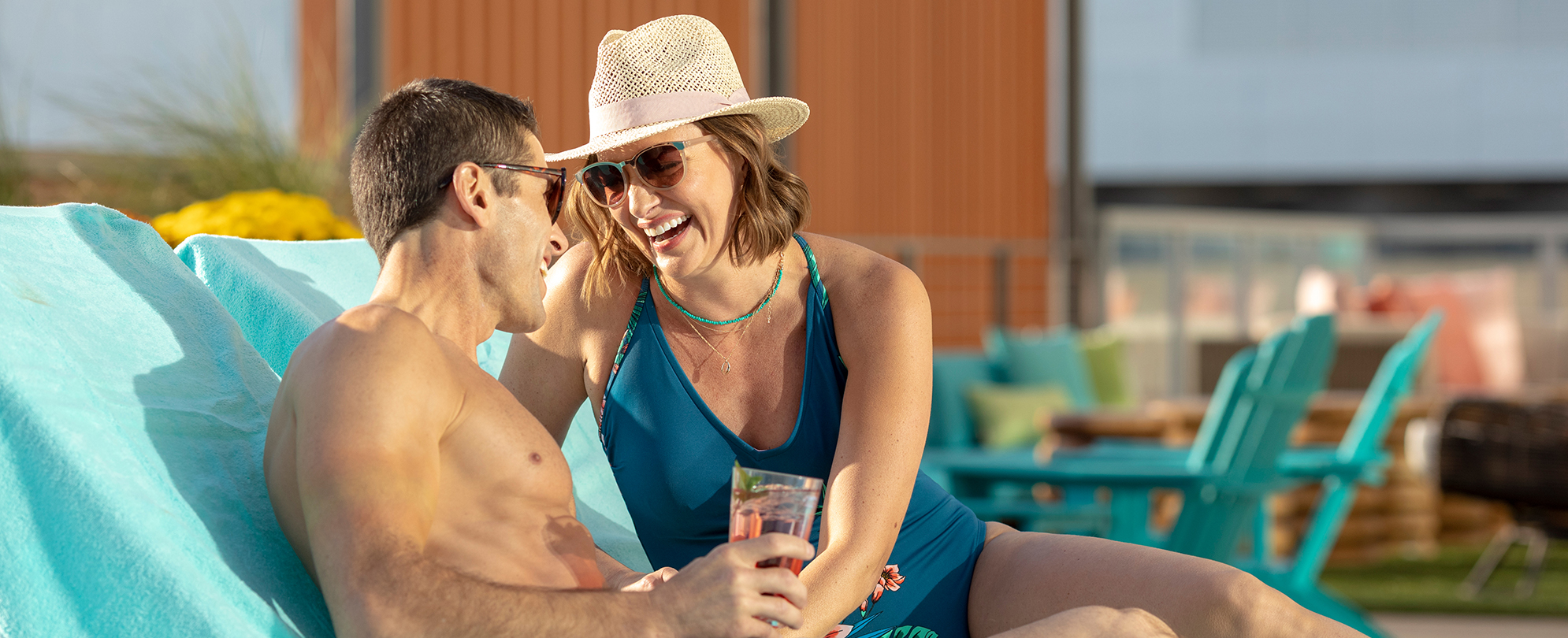 Man and woman wearing sunglasses laugh and drink by the pool at a Margaritaville Vacation Club resort.