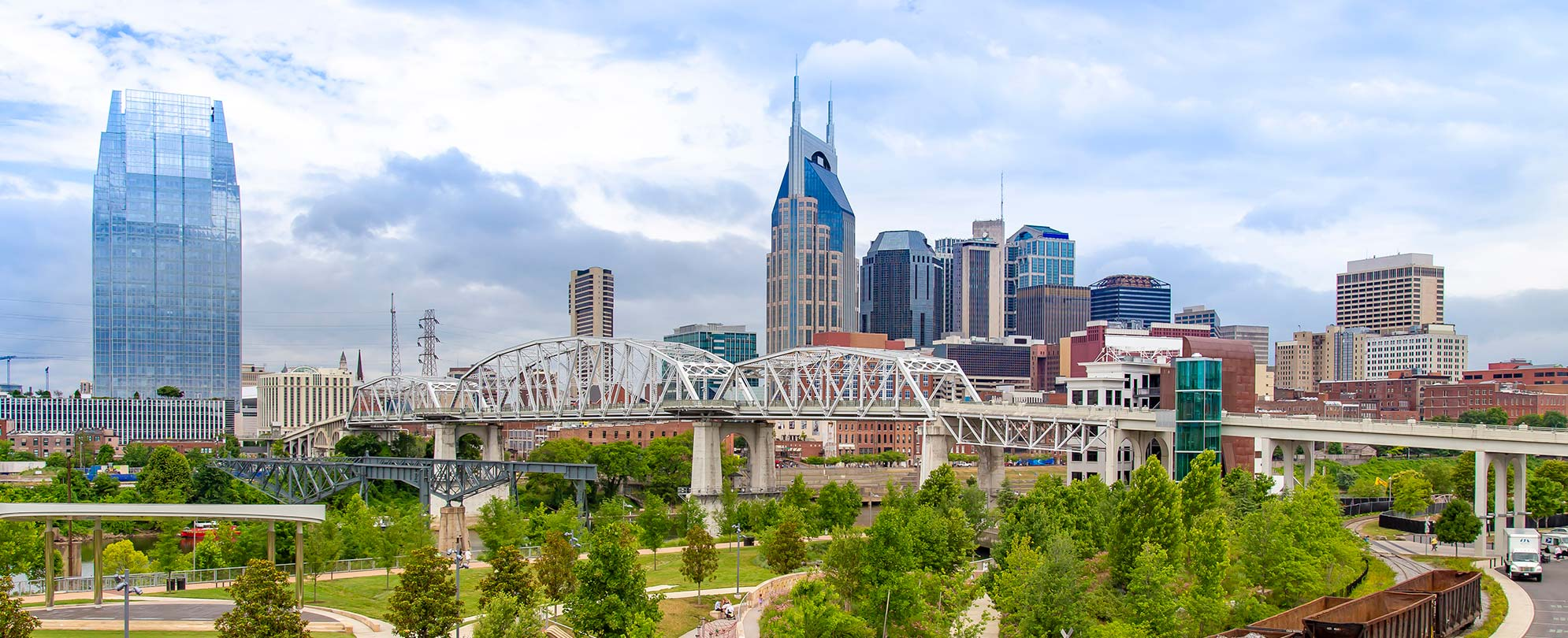 The pedestrian bridge and city skyline of Nashville, Tennessee on a clear, sunny day.