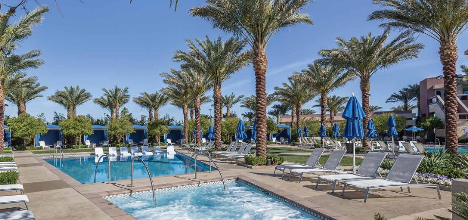 Blue chairs, umbrellas, and cabanas surround the pool and hot tub at Margaritaville Vacation Club by Wyndham - Desert Blue.