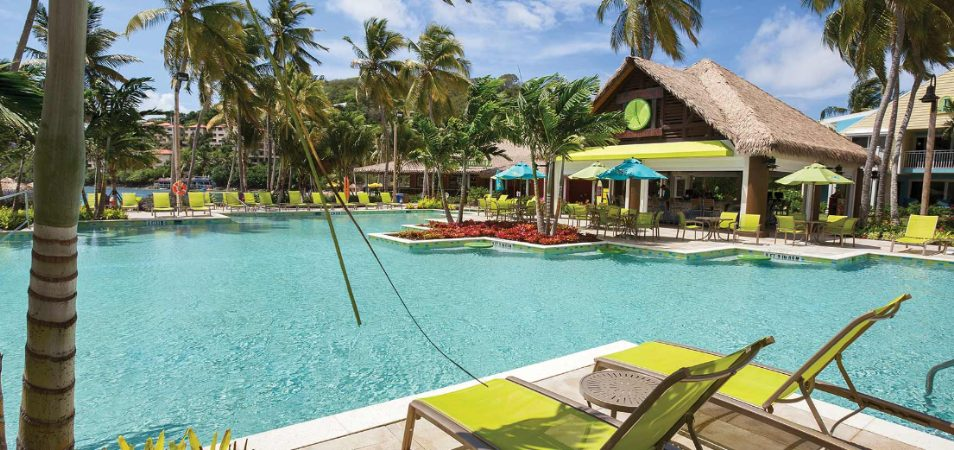 Bright green pool chairs and palms surround the pool and tiki bar of Margaritaville Vacation Club by Wyndham - St. Thomas.