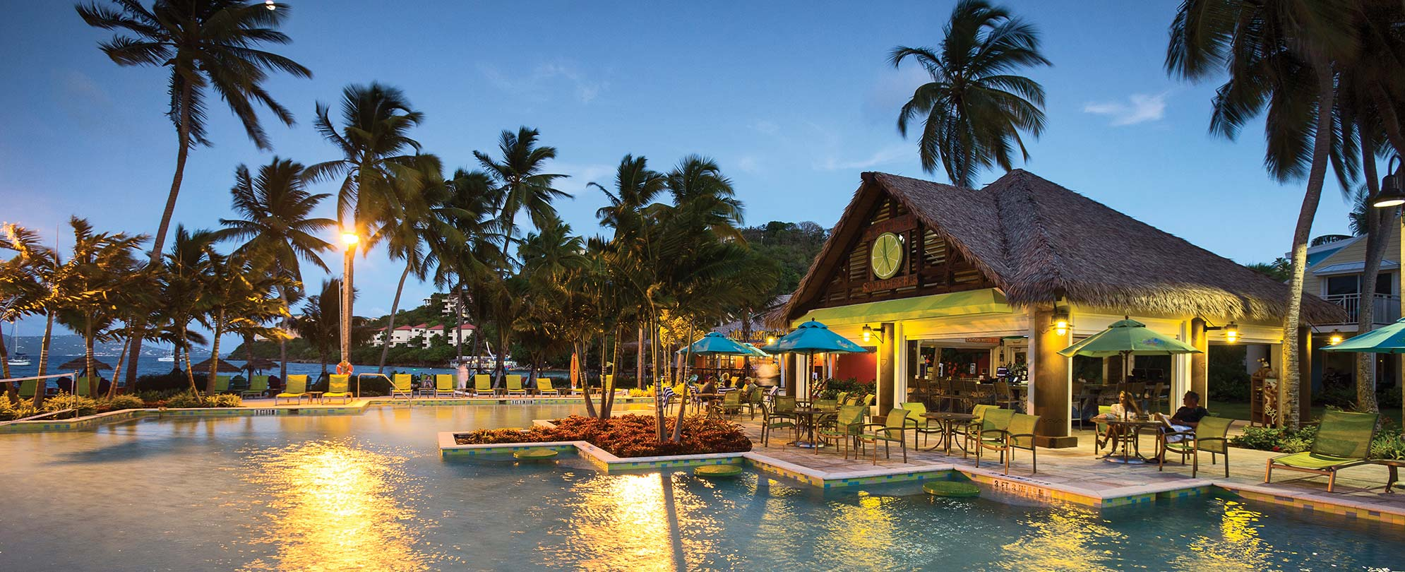 The oceanfront pool and tiki bar in the evening at Margaritaville Vacation Club by Wyndham - St. Thomas, a timeshare resort.