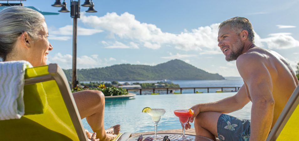 Man and woman sit by an oceanfront pool drinking red and green margaritas at a Margaritaville Vacation Club resort.