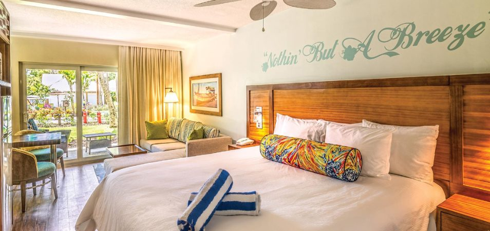 """Nothin' But A Breeze"" written on the wall above a resort bed with a wood headboard in a Margaritaville Vacation Club suite."