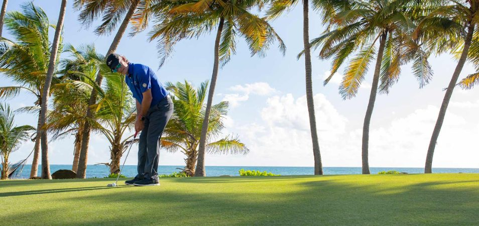 Man in a blue polo putting a golf ball at an oceanfront golf course near a Margaritaville Vacation Club resort.