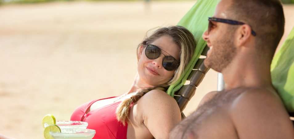 A couple relaxes in pool chairs while drinking margaritas at a Margaritaville Vacation Club resort.
