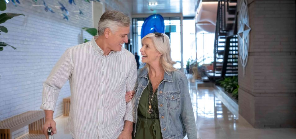 Smiling older man and woman walking through the lobby of a Margaritaville Vacation Club resort.