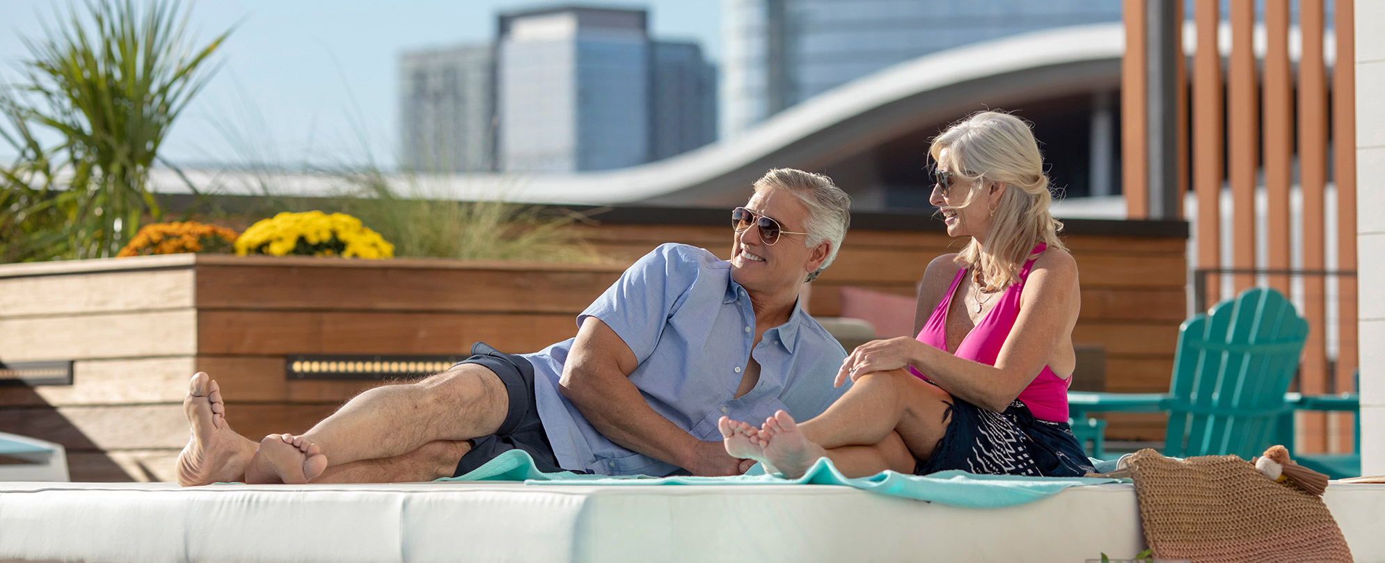 Smiling older man and woman lay in pool chairs by the rooftop pool at Margaritaville Vacation Club by Wyndham - Nashville.