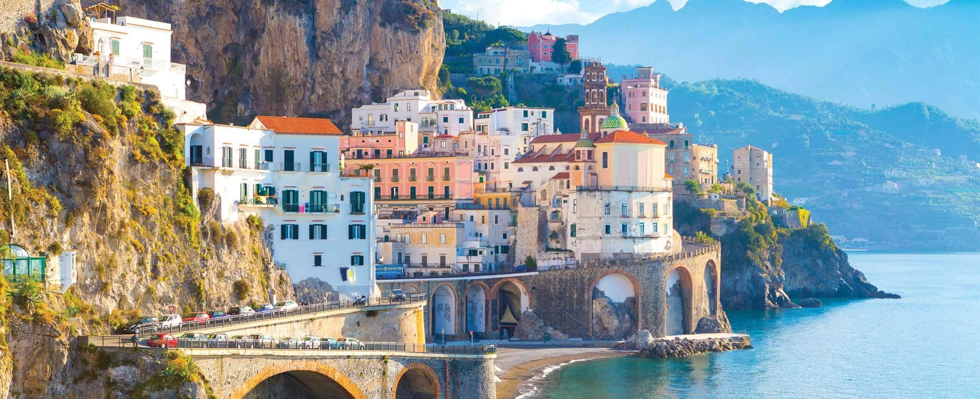 Italy's Amalfi Coast, with colorful buildings and roadway built into the waterfront mountainside.