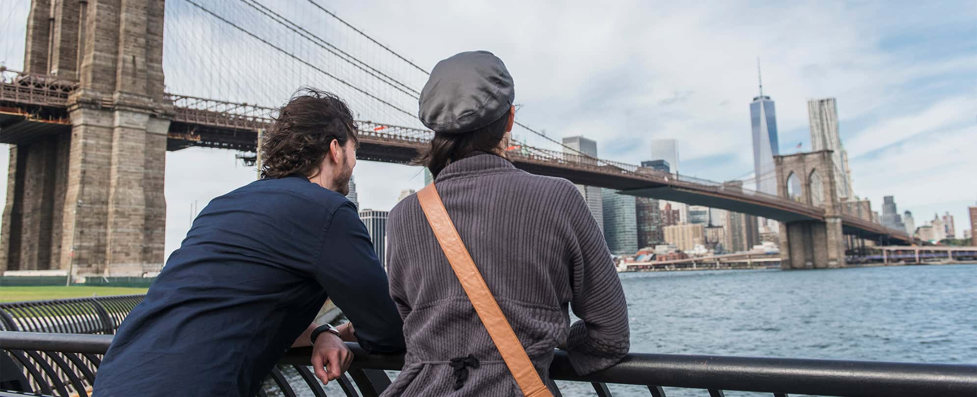 Man and woman leaned over railing, taking in the view of the New York City skyline and Brooklyn Bridge.