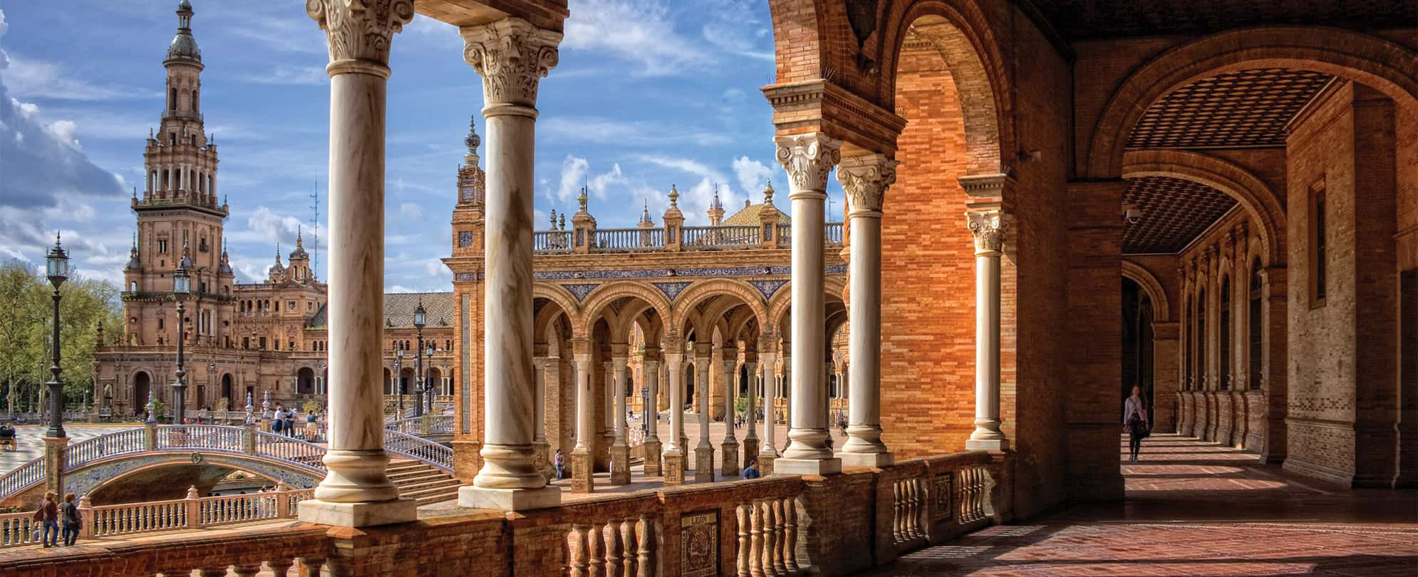 Marble columns, tall tower, and red stone architecture at the Plaza De Espana in Spain