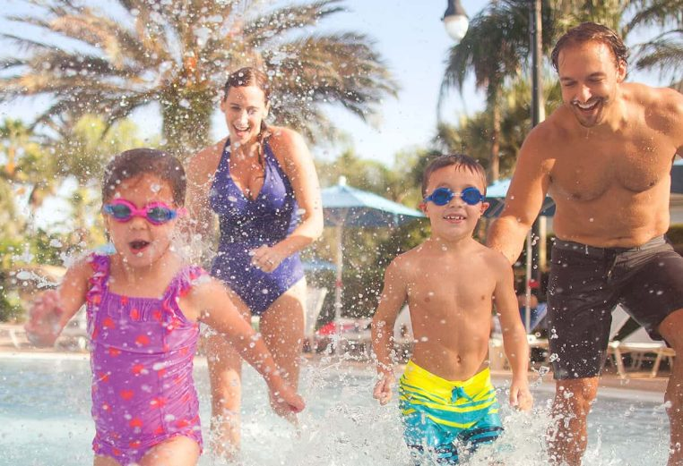 Parents with two young kids wearing goggles run through a splashpad at a timeshare resort.