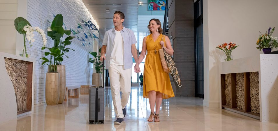 Man rolling suitcase and woman in yellow dress hold hands and walk through the lobby of a Mararitaville Vacation Club resort.
