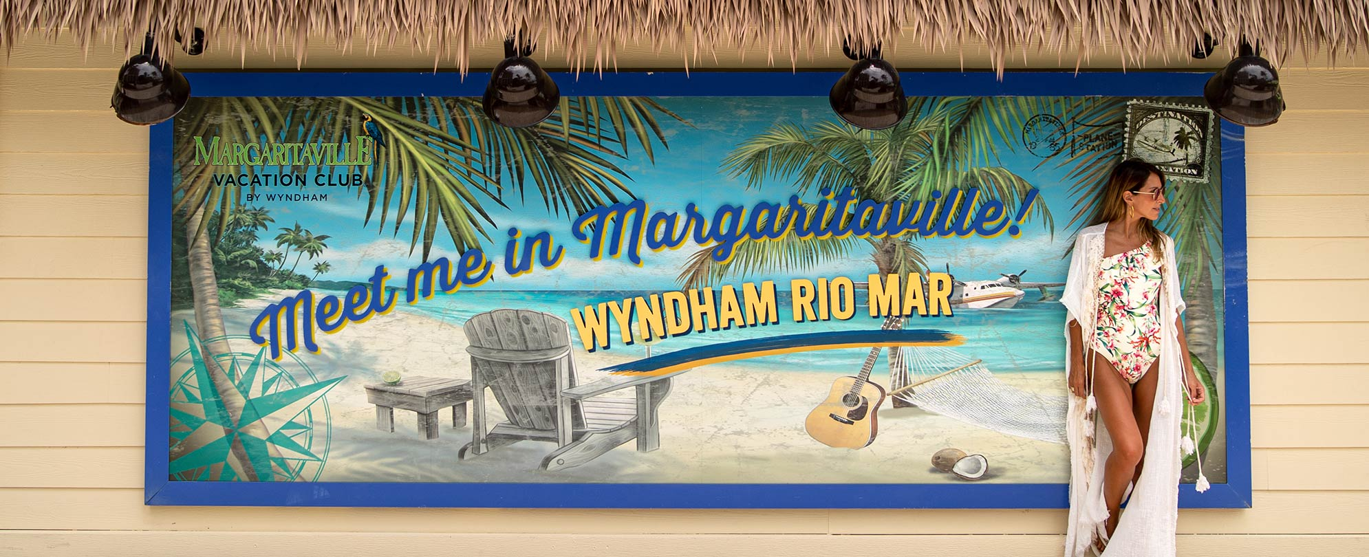"Woman standing by of sign that reads ""Meet Me in Margaritaville. Wyndham Rio Mar"" at a Margaritaville Vacation Club resort."