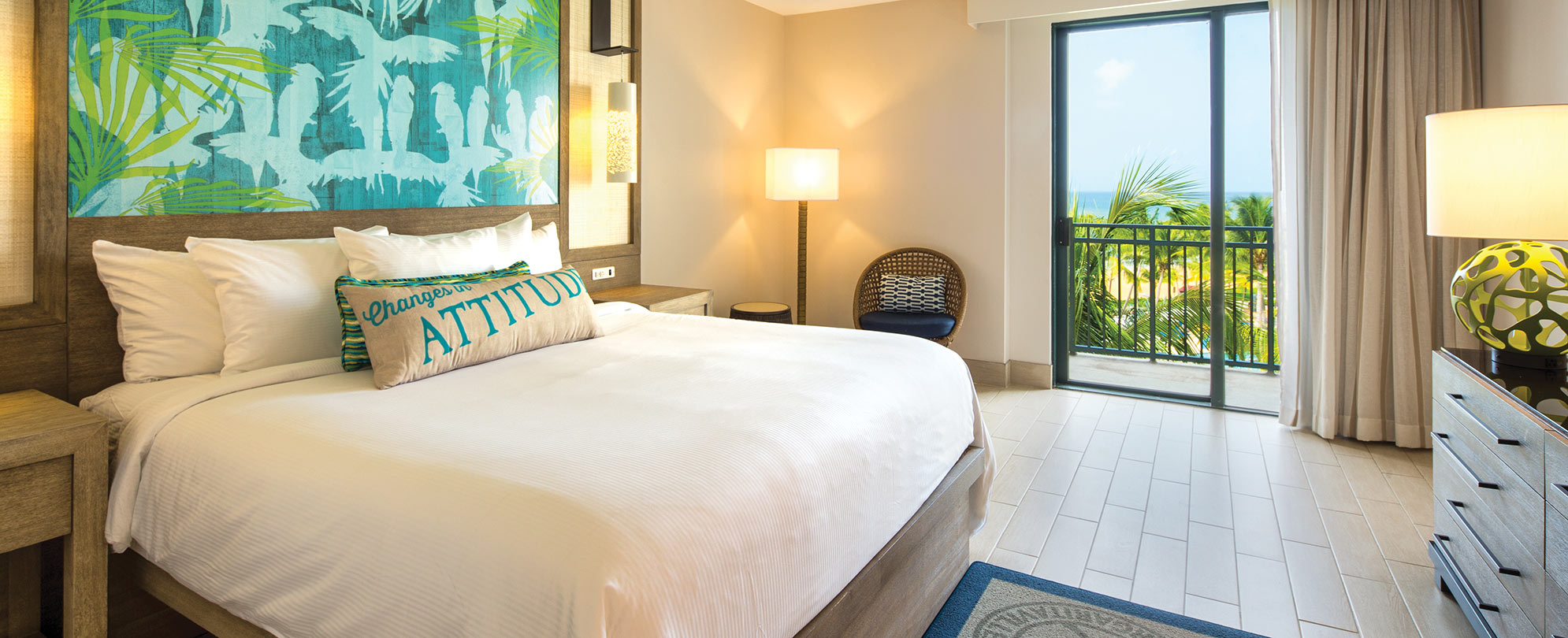 A king-size resort bed with crisp white linens in a Margaritaville Vacation Club suite with an ocean view.