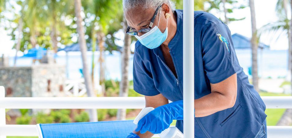 Female employee wearing a blue medical mask and gloves sprays down a table at a Margaritaville Vacation Club resort.