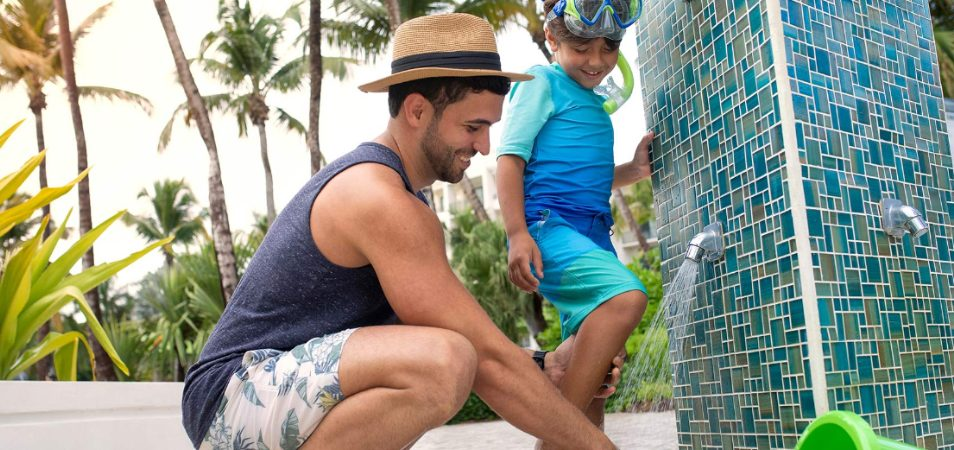 A dad helping his son wash sand off his feet in an outdoor shower at a Margaritaville Vacation Club resort.