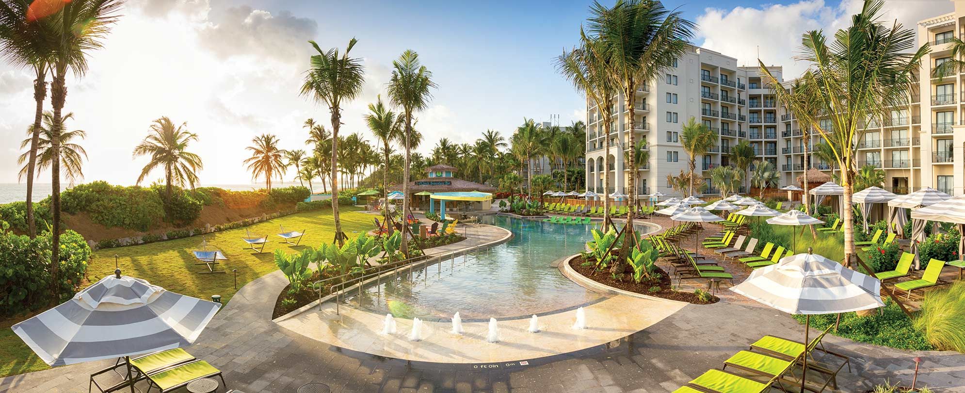 A zero-entry pool with fountains at Margaritaville Vacation Club by Wyndham - Rio Mar, an oceanfront timeshare resort.