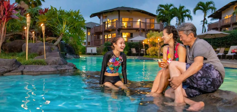 Mom, dad, and daughter sit on rocks in a Margaritaville Vacation Club Resort pool at night, tiki torches lit behind them.