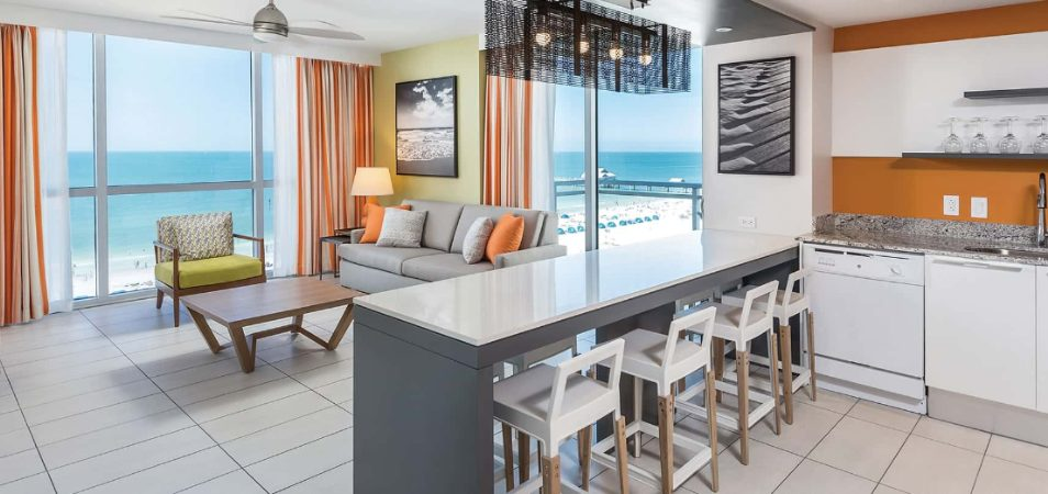 A modern living room and kitchen in a Margaritaville Vacation Club suite with a view of the ocean.