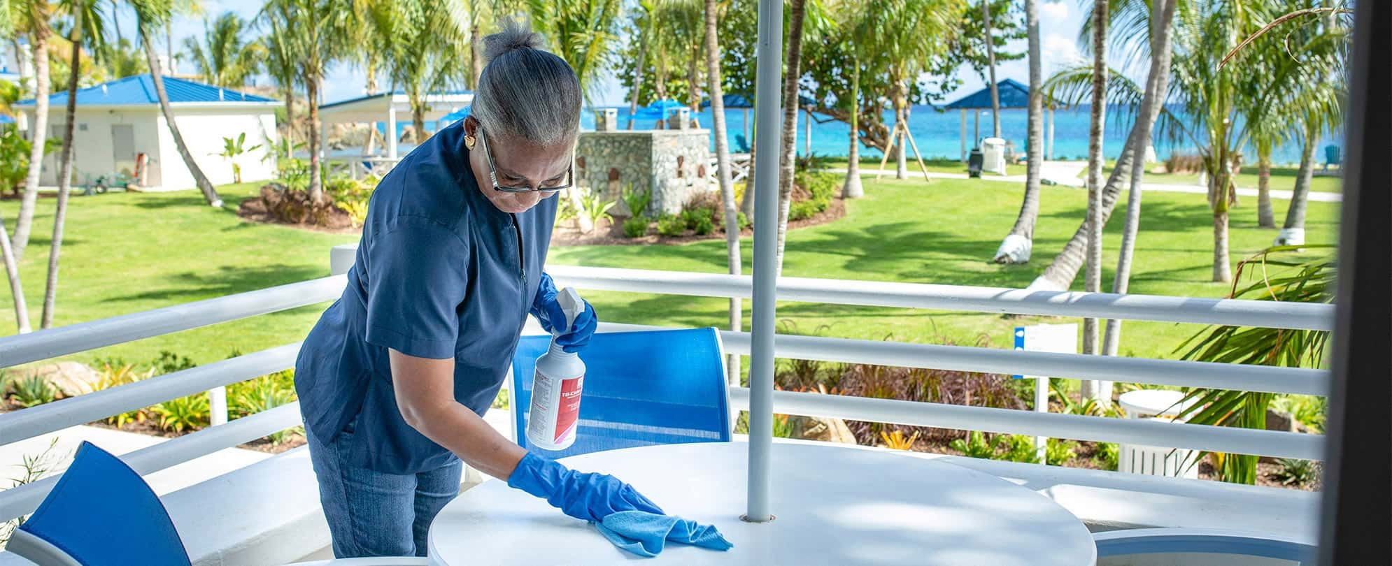 Female employee wearing a blue medical mask and gloves wipes an outdoor table at a Margaritaville Vacation Club resort.