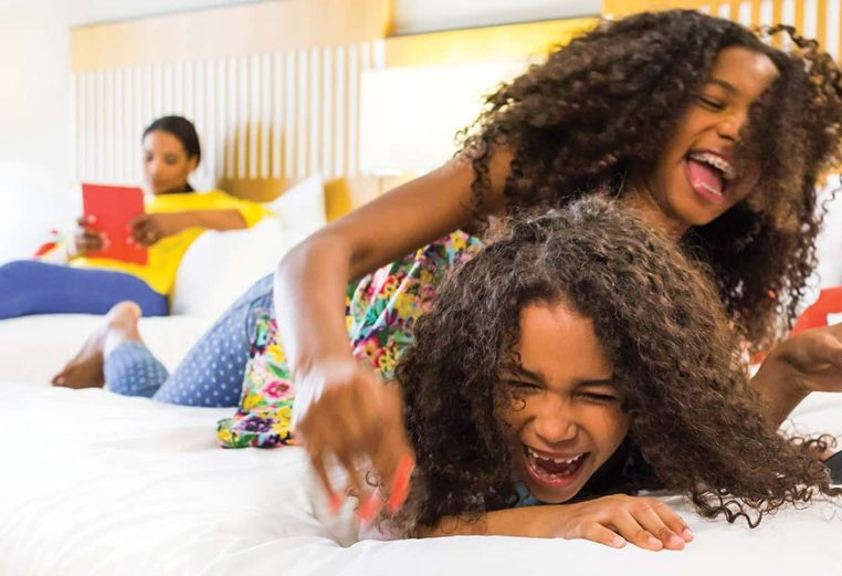 Two smiling young girls with dark, curly hair wrestle for remote on the bed of a Margaritaville Vacation Club Resort suite.