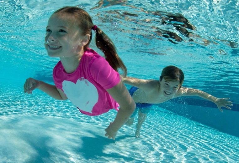 A smiling young girl and boy swim underwater in a pool while enjoying vacation.