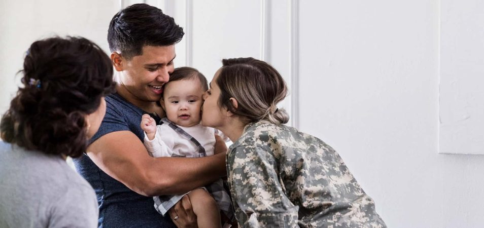 A grandmother lovingly watches a father holding baby while a military mom leans over to kiss the child on the cheek.
