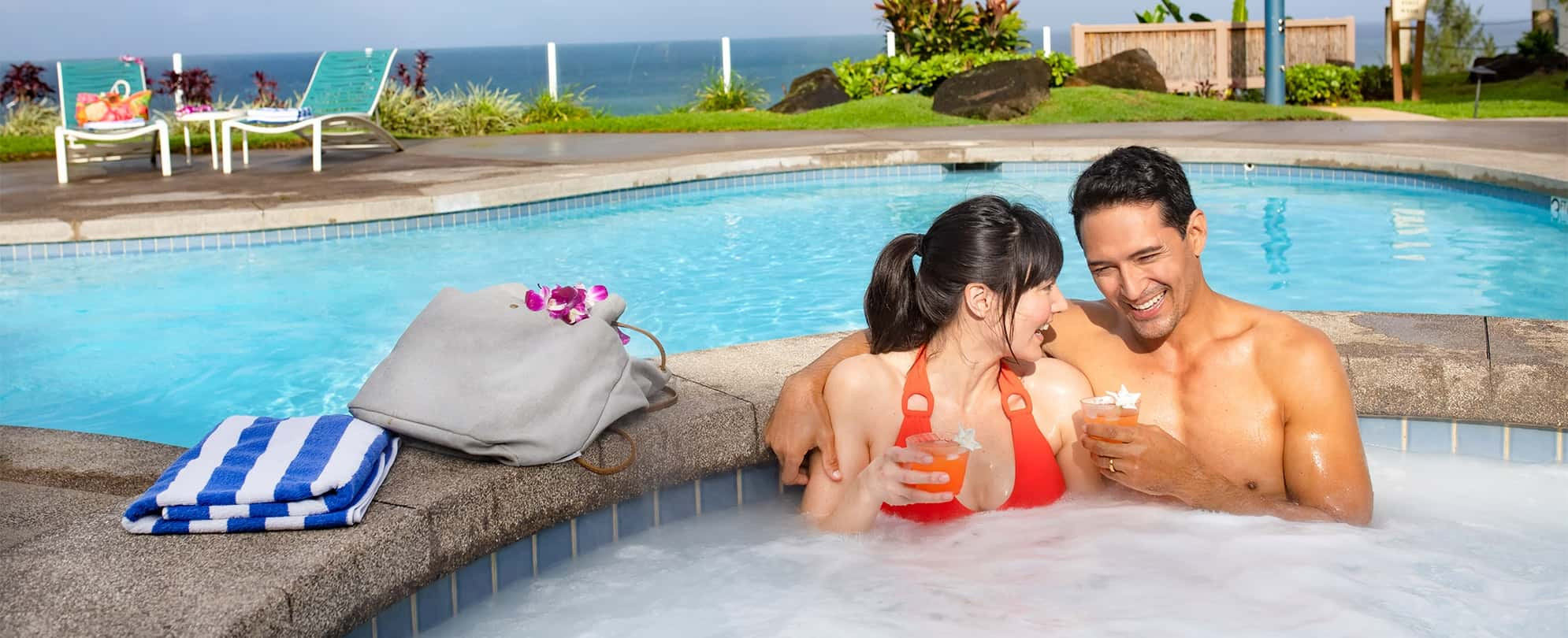 Husband wraps his arm around his wife as they enjoy drinks in a hot tub of a Margaritaville Vacation Club resort.