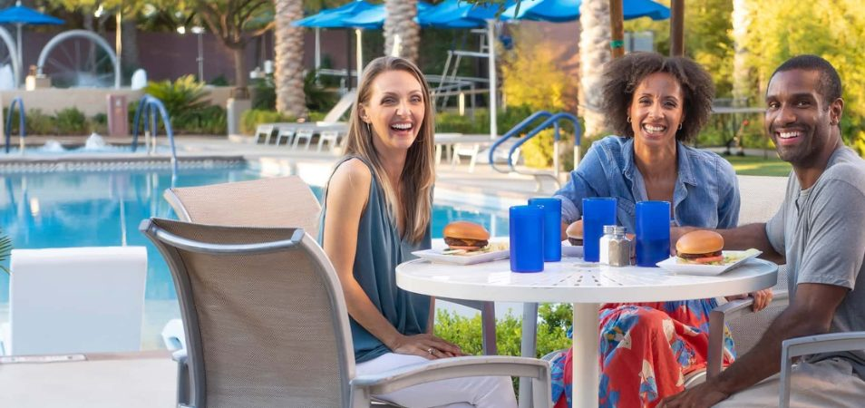 Three smiling adults enjoy burgers and drinks in blue cups at a poolside table of a Margaritaville Vacation Club resort.