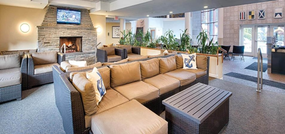 Wicker couches with tan cushions and fireplace in a Margaritaville Vacation Club by Wyndham resort lobby.