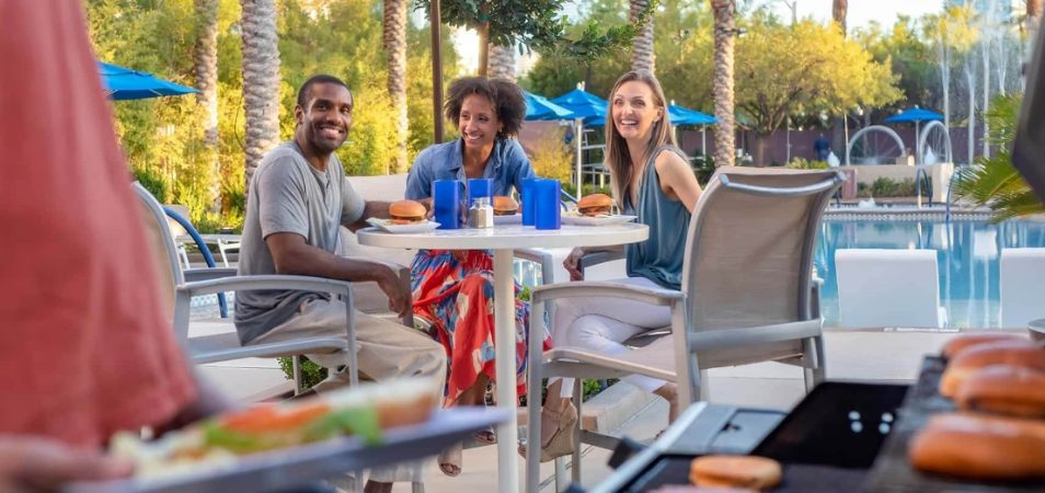 Three adults sitting at a poolside table enjoy grilled burgers at a Margaritaville Vacation Club resort.