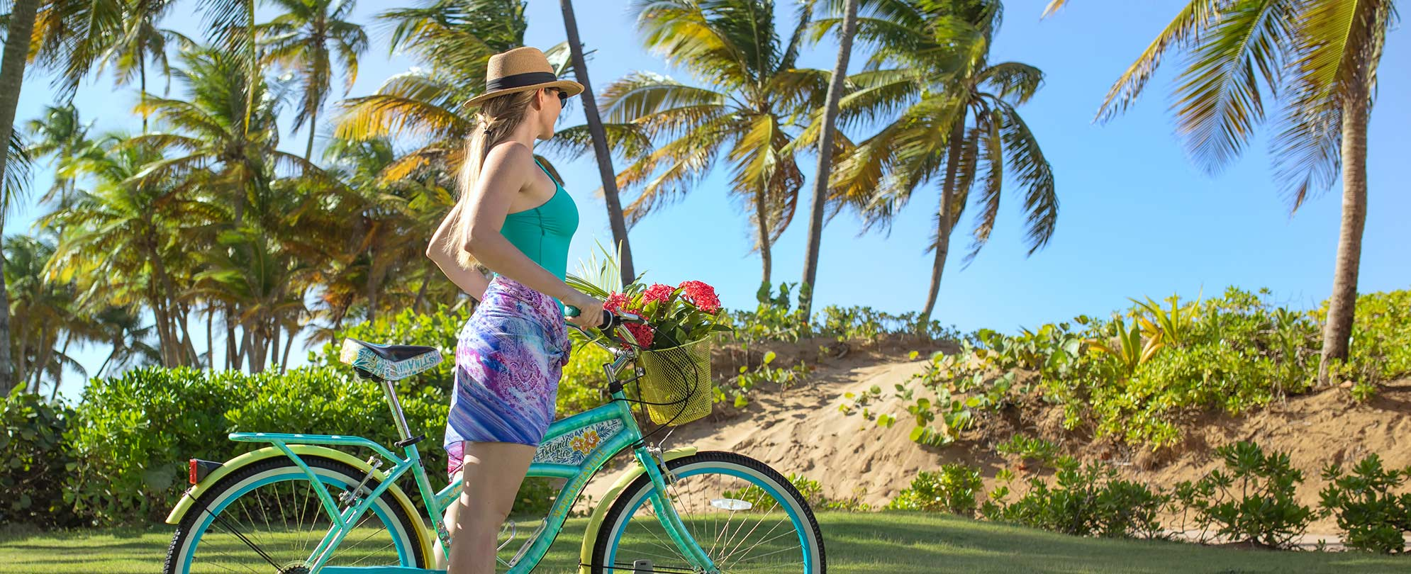 Woman standing holding a teal bike, looks out at the palm trees while vacationing at a Margaritaville Vacation Club resort.