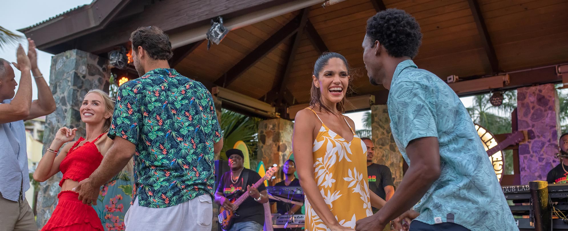 Men and women enjoy a warm winter vacation, dancing in front of a live band at a Margaritaville Vacation Club resort.