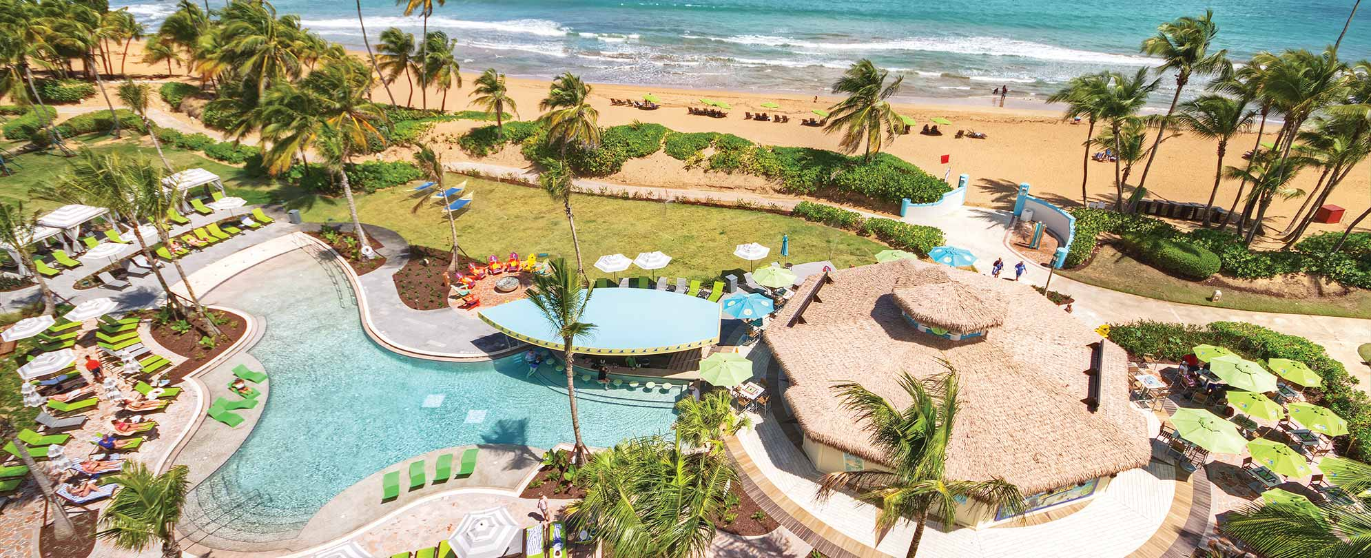 Birds-eye-view of the ocean and pool, with a boat-shaped swim-up bar, at Margaritaville Vacation Club by Wyndham - Rio Mar.